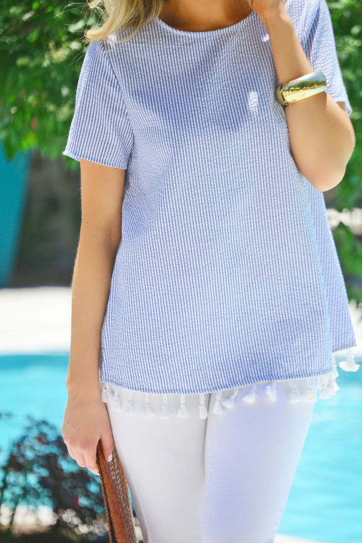 This top makes our seersucker dreams come true by pairing the classic look with tassel trim! Top has a keyhole detail in the back. Fabric is a breathable cotton-blend.