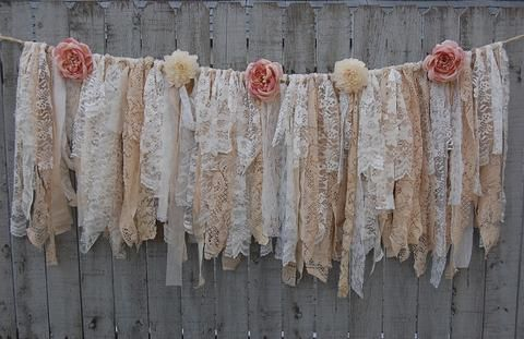 Shabby chic garland, hand tied with tattered tea stained and ivory lace, crepe, brocade and linen and accented with ivory and soft pink flowers. The flower stems are woven into the top to keep them se