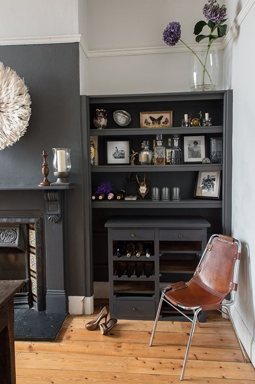 Victorian home in Bristol,  the wall is painted in soft black and an old cupboard turned into a drinks cabinet. Cream Juju hat above the fireplace and the leather and chrome chair is a Les Arcs chair by Charlotte Perriand.