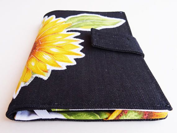 Practical and beautiful solution for your eBook reader. Outside - case is made of dark denim - applique fabric element in front - case is closed with a tie and Velcro closure  Inside - printed fabric with sunflowers - main pocket to kept the eBook when is not written - eBook reader is kept with 2 rubbers (left) and 2 triangle pieces (right) to protect not fall out - vertical pocket for notes or small cables For convenience the case can be fold in half when reading the eBook. This eBook case…