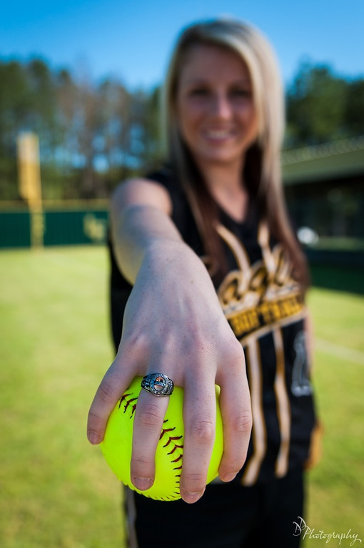 Softball girl with softball  in her hand with classring, only if she would hold the ball on the seams, really?