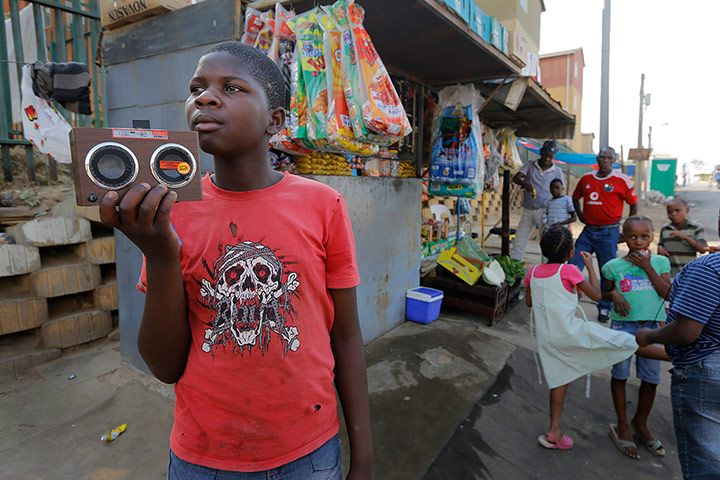 A boy listens to his radio next to a fruit seller's stand. Credit: Kim Ludbrook/EPA