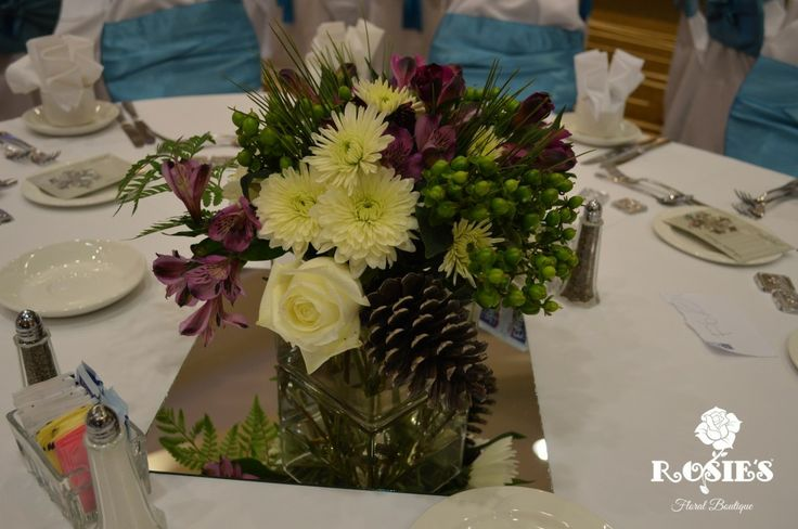 Cube Vase made with chrysanthemums, green hypericum, roses, alstroemeria and pinecones. Vase filled with blueberries! Flowers and Picture by Rosie's Floral Boutique. #roses #centerpiece #event #wedding #alstroemeria #pinecone #chrysanthemums
