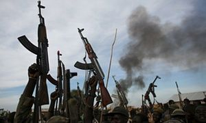Rebel fighters hold up their rifles as they walk in front of a bushfire in Upper Nile State, South Sudan, in February 2014. The civil war is now entering its third year.