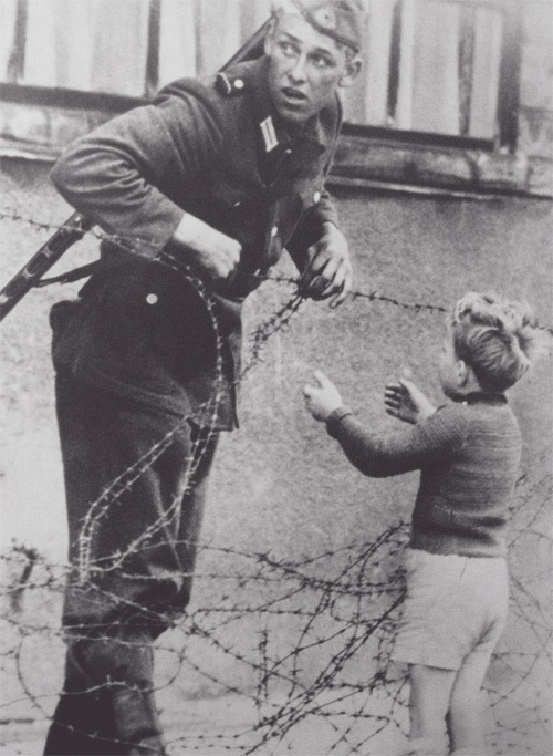 An East German soldier helping a boy cross the newly formed 'Berlin Wall,' 1961. The boy was found on the opposite side of the wall from his family. Despite given orders by the East German government to let no one pass, the soldier helped the boy through the barbwire.