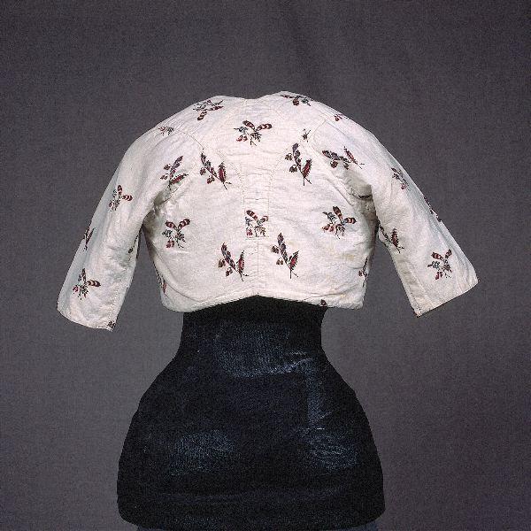 spencer 1790-tal Vit med strödda, tryckta blombuketter i rött, rosa, blått, lila och mörkbrunt. Fodrad med vit linnelärft. Saknar knäppning.