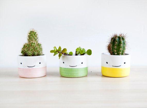 Cache-pots en céramique mignons fait à la main appelé Manolitos. Lot de pots de plante en céramique trhee parfaits pour donner une touche de couleur et de plaisir à votre bureau, étagère ou de table. Ce petits planteurs sont vraiment doux et brillant à l'intention des plantes succulentes de cactus qui juste besoin de l'eau  Vous pouvez planter vos succulentes directement à l'intérieur de la jardinière ou utiliser un petit pot en plastique. Je recommande de planter la plante directement pour…