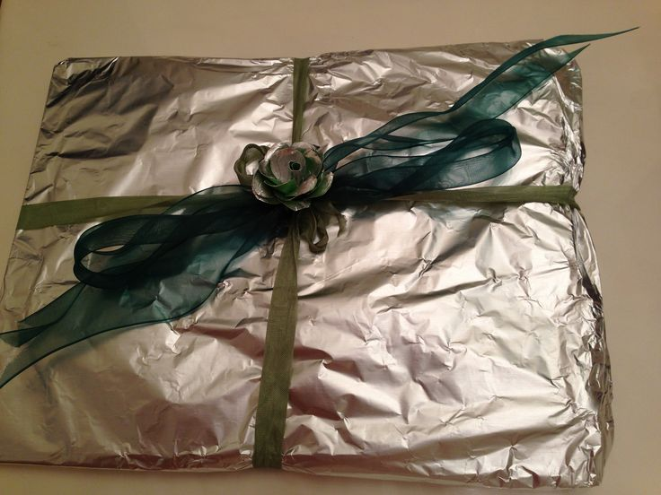 "Tenth anniversary is the ""Tin"" or aluminum anniversary. I wrapped the gift in aluminum foil and them made an aluminum foil rose to add to the ribbon. So fun!"