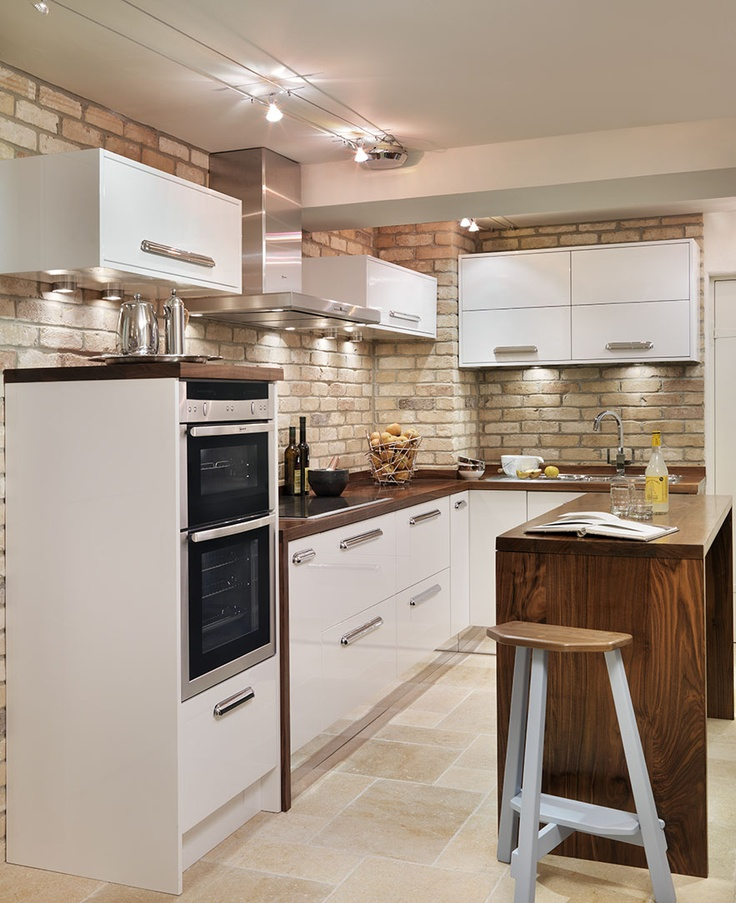 Cool basement kitchen in gloss white paint with Walnut surfaces.