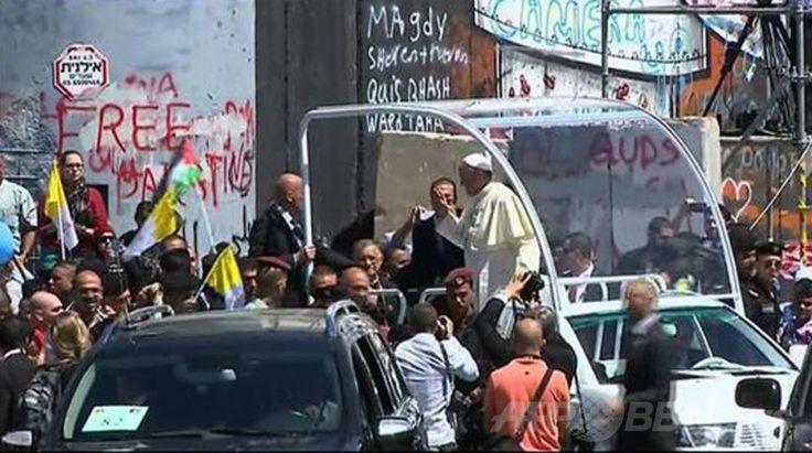 パレスチナ自治区ベツレヘム(Bethlehem)で、白いオープンカーで移動中にイスラエルが建設した分離壁の前で止まり、群集に手を振るローマ・カトリック教会のフランシスコ(Francis)法王(2014年5月25日撮影)。(c)AFP/PALESTINIAN TV ▼25May2014AFP|中東歴訪中のローマ法王、ベツレヘム到着 http://www.afpbb.com/articles/-/3015852 #Bethlehem #Pope_Francis #Papa_Francisco #Papa_Francesco #البابا_فرنسيس