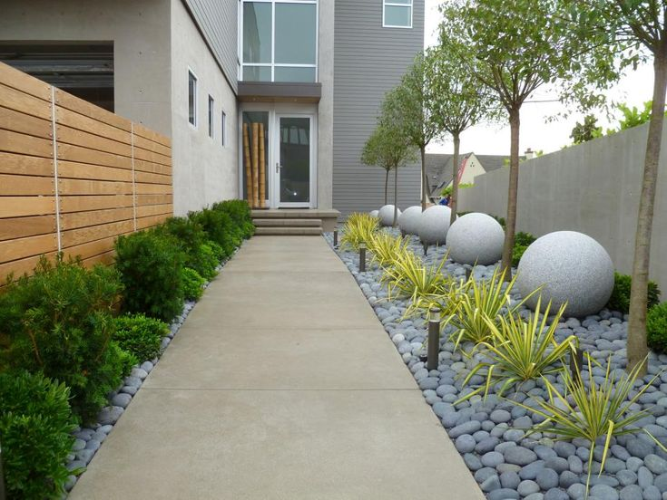 Small shrubs line one side of the walkway to this contemporary home. On the other side, black flat river rocks ground rows of variegated yucca, granite orbs and globed cherry trees.