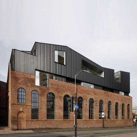 The two storeys that Project Orange have added to the roof of a redundant brick warehouse in Sheffield look like another building stacked on top.  The upward extension replaces a pitched roof, creating three duplex studio offices within a powder-coated steel volume that both overlaps and bites through the original brick structure.  A new restaurant and bar occupies the double-height warehouse space below, where it benefits from light through the original two-storey-high arched windows.