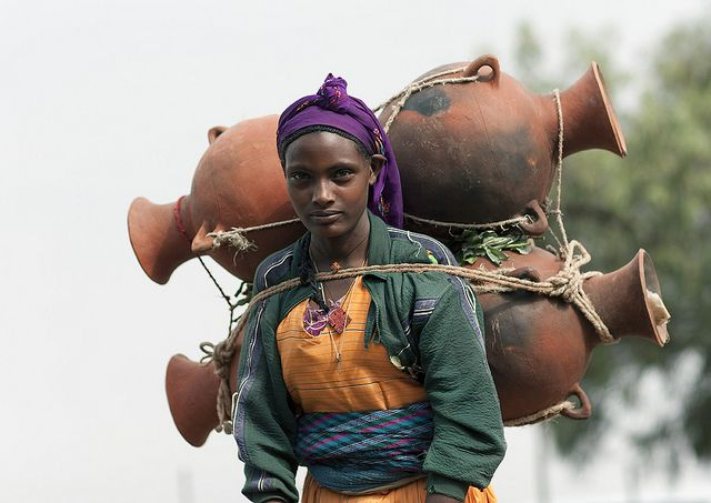 Oromo woman carrying jars on her back, Tulugulu village, Ethiopia.  Sometimes, ethiopian women carry more than donkeys. Hard life in the countryside ... // by Eric Lafforgue