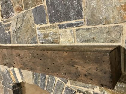 Per our client's request, this original mantel was built using reclaimed pine. The 150-year-old wood was hand-brushed and cleaned, but left unstained to showcase its beautiful, weathered patina. This type of look is unique to naturally aged wood, always specific to the individual piece. Their fireplace mantel will serve as both a useful focal point and interesting conversation starter for years to come.
