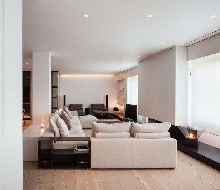 Soggiorno contemporaneo moderno con arredi e mobili colore bianco crema e marrone scuro. Camino aperto, tv e pavimenti in legno