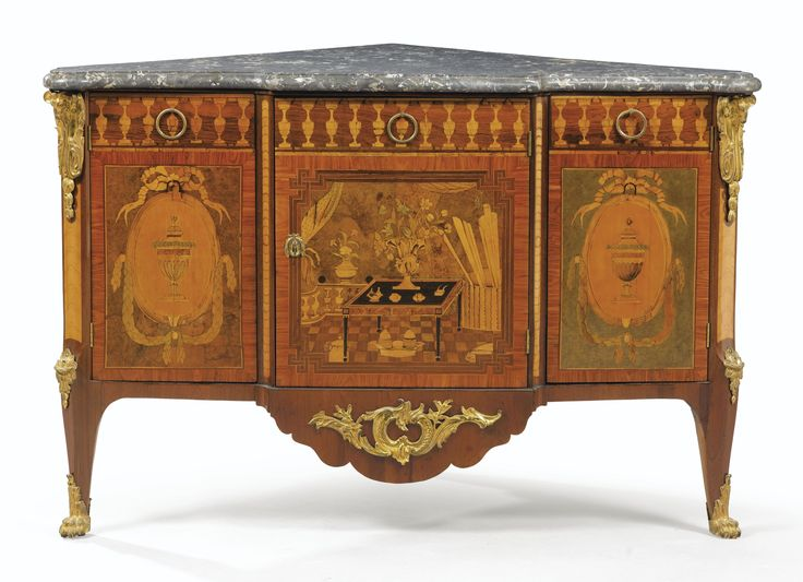 Una comoda esquinera con marquetería y aplicaciones de bronce dorado, estilo Luis XVI, firmada Topino y JME, cerca de 1780.