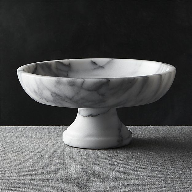 French Kitchen Marble Fruit Bowl DETAILS A substantial bowl of cool white marble with unique grey veining rests atop a traditional pedestal for a grand presentation of fruits and decorative objects. Note that exposure to the acid of cut citrus fruits can stain marble.