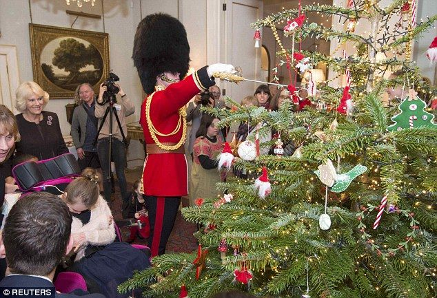 Captain Matt Wright of the Welsh Guards hangs a Christmas decoration with his sword on Camilla's tree