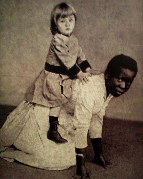 """Escrava brasileira serve de """"cavalinho"""" para criança branca. Esta fotografia, datada do final do século 19, tem uma carga simbólica imensa e pode ser relacionada com inúmeros eventos violentos ocorridos no Brasil durante os séculos posteriores."""