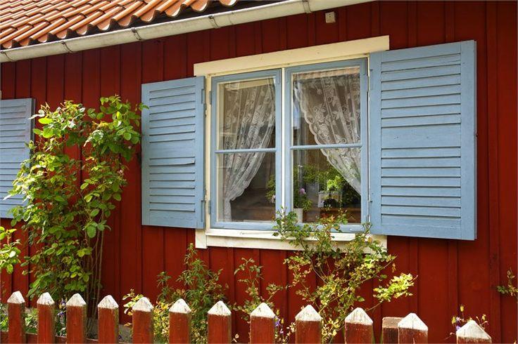 Fönsterluckor på falurött hus