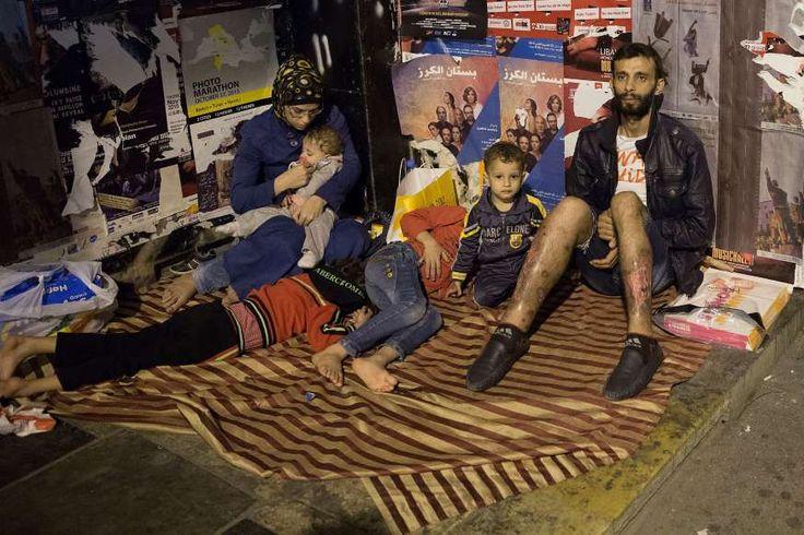 Een gezin met vier kinderen, gevlucht uit Syrie, zit op straat en bedelt om geld bij het uitgaanspubliek in Beiroet.