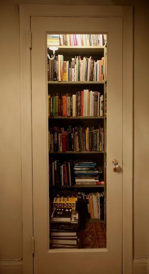Hall closet + shelves + overhead light + glass door = perfect tiny home library.