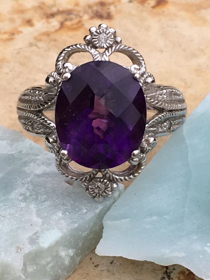 14k white gold ring set with a large deep purple amethyst that weighs approximately 4 carats. The lacy setting is set with small diamonds. Stones have been tested with a gem tester. Size: 7 1/8 Measur