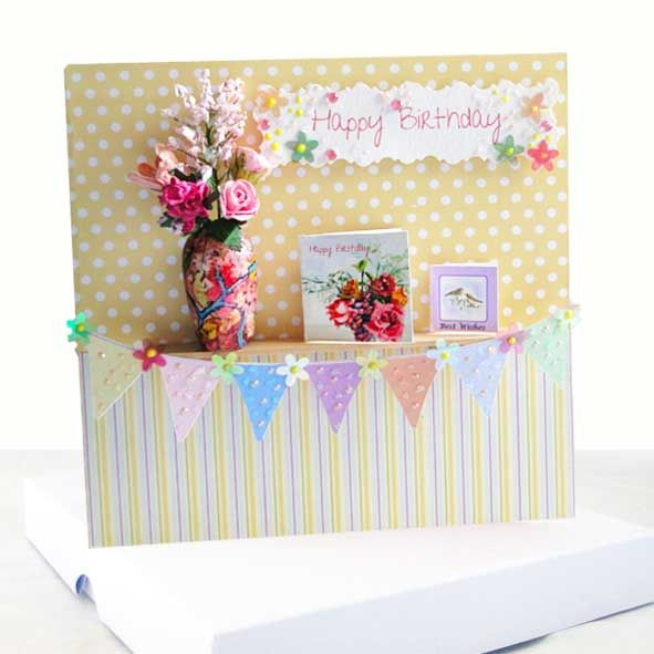 A luxurious 3-Dimensional Floral Birthday Card with an ingenious miniature theme in multi colours but mainly yellows and pinks.  The design has a real handcrafted miniature ceramic miniature vase with a flower arrangement of mixed miniature flowers and miniature birthday cards arranged as if on a real wooden shelf or mantelpiece. With hanging Birthday bunting finished with added sparkle and gems.