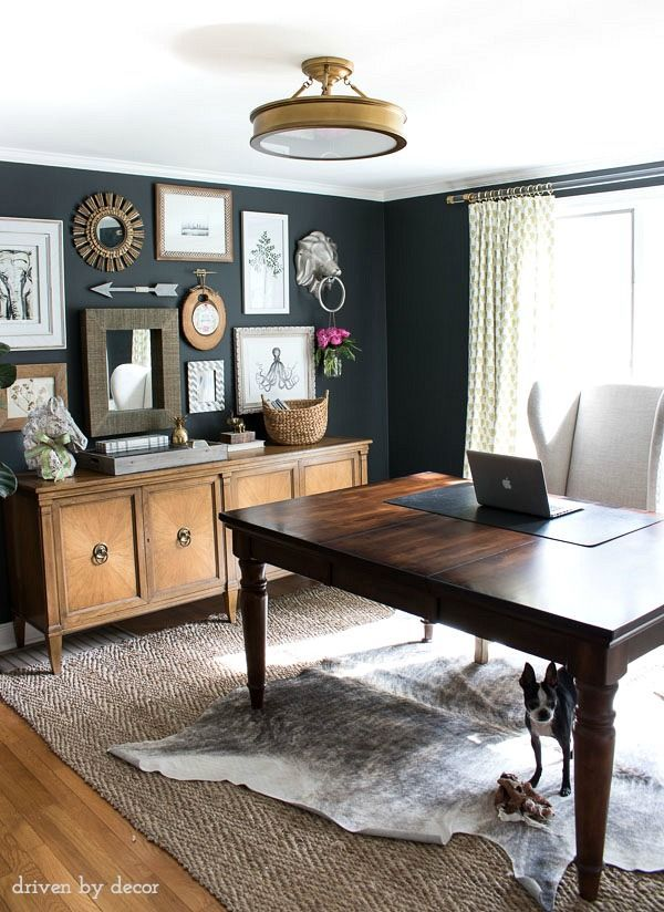 Home office with charcoal gray walls and eclectic gallery wall above a credenza