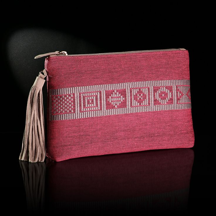 Τhe handmade woven envelope adorns patterns from Greek history and tradition. The background is in pink color and the embroidery in grey color.