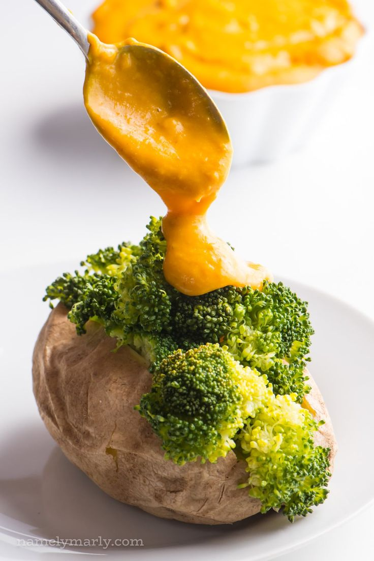 A spoon is drizzling vegan cheese sauce over a baked potato with steamed broccoli. A bowl of more cheese sauce is sitting in the background.