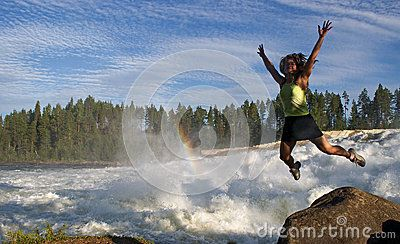 Young woman jumping  near waterfall Storforsen in Sweden