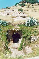 """dromos d'accesso della domus di janas   tomba dei vasi tetrapodi.  All'interno di questa sola tomba si sono trovati 447 reperti, appartenenti a tutte le culture preistoriche sarde.  La sua costruzione originaria è databile alla cosiddetta """"cultura di Ozieri """" (3500 a.C. circa)."""