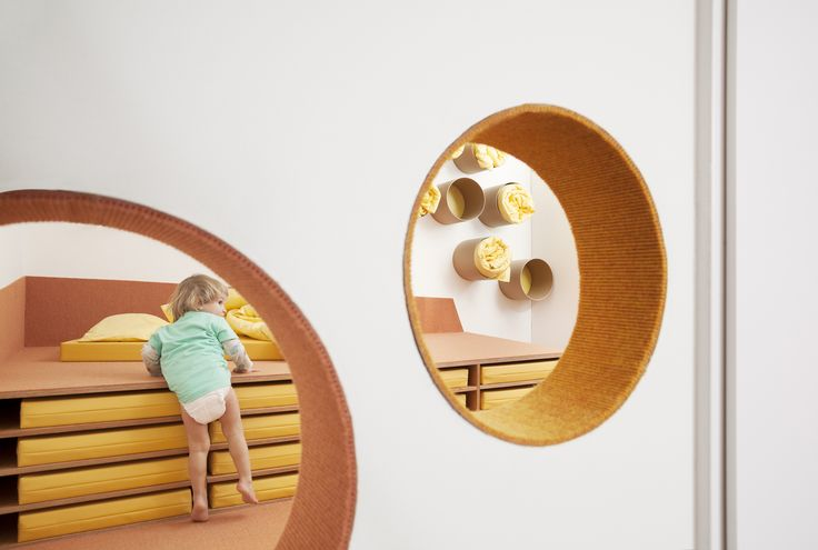 Sinnewandel Kindergarten in Berlin designed by Baukind and Atelier Perela. Circular cut-outs playfully connect space.