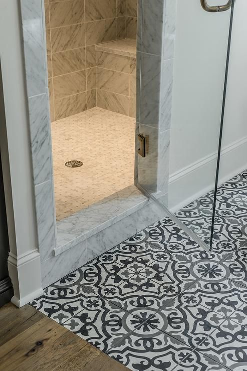 black and white mediterranean bathroom features a white gray and black mosaic tiled floor placed before a walk in shower clad in mixed marble tiles