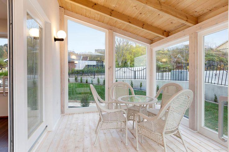 Delvis inglasad altan med fönster från golv till tak för mycket ljus och trä på golvet.