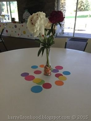 Decoration ideas for a Baby Sprinkle Shower, centerpieces with flowers in a vase filled with sprinkles and colored polka dots scattered on table