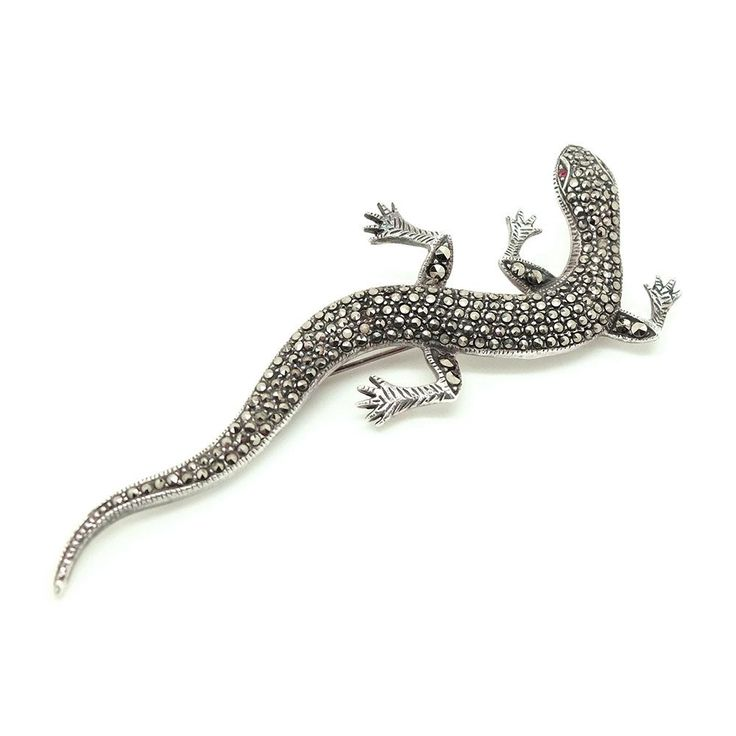 Art Deco 1920s silver lizard brooch featuring stunning faceted marcasite stones over the body and legs. This life like brooch is set with bright orange eyes. Marcasites are actually Pyrite also known as Fools Gold. It was used in jewellery due to its ability to catch the light, giving a diamond effect.   Lizard jewellery became very popular in the Victorian era and continued into the 1920s. The Victorians enjoyed novelty pieces which included many different types of animals.   SYMBOLISM…