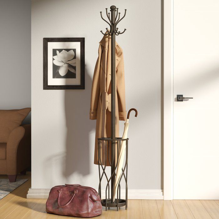 A contemporary update on a traditional design, this freestanding coat rack is an excellent addition to your elegant entryway. Made from stainless steel in a tasteful brown finish, this dapper design features two tiers of gently curved hooks for scarves, hats, jackets, and totes, and a built-in umbrella stand with swirling ironwork details to place your parasols. For an inviting space to greet your guests, roll out a trellis-print area rug in the center of the foyer, then set this design…