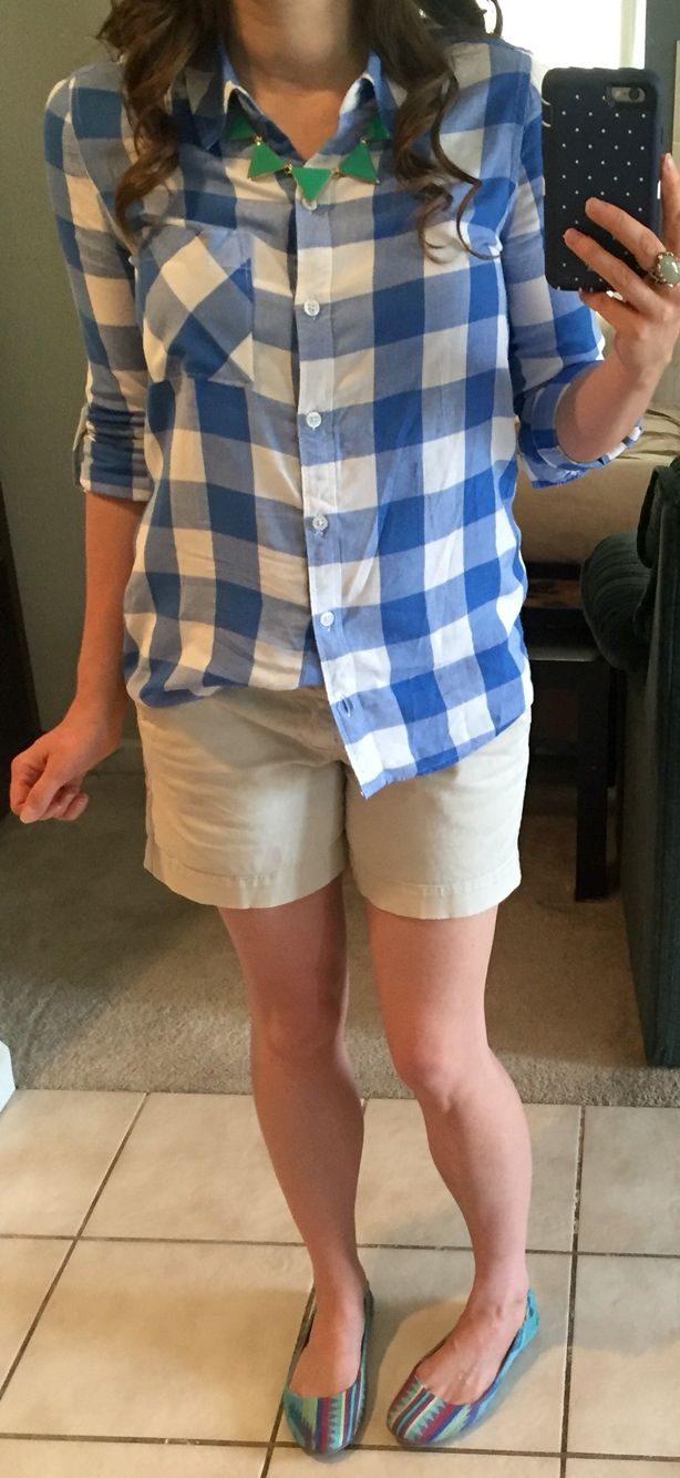 Green triangle necklace, blue and white buffalo check button-up shirt, khaki shorts, multicolored Aztec flats.