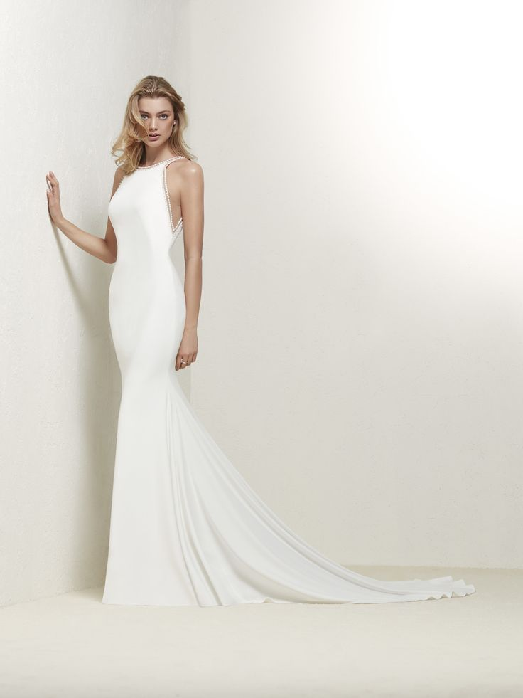 Drabea: Elegant mermaid style wedding dress with halter neck and V back. Decorated with a fine outline of gems. Pronovias