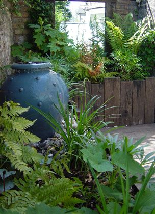 A Weathered Retreat    A few pebbles threaded on a frayed, weathered string, triggered the inspiration for this tiny courtyard garden. My client had picked them up from a beach in Suffolk where the grasses on the sand dunes billow in the sea wind. The crumbly old brick wall cried out for weathered