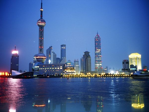 Beautiful city to visit. Water reflects Shanghai's distinctive skyline in this view of the city and riverfront at night.