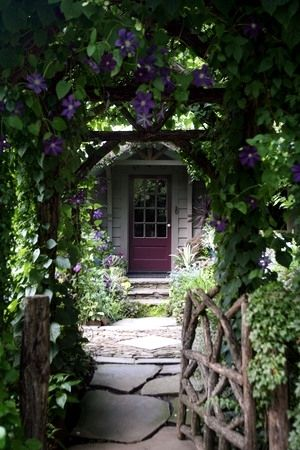 A wooden arbour with purple clematis rambling over invites you to step in. It's almost a secret hideaway!