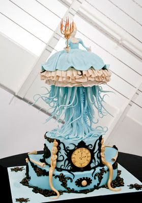 """Inspired by the painting """"Descent"""" by Ray Caesar, this cake by Dante Nuno of Fire and Icing features a lady with a squid dress and trident, standing astride an antique looking clock."""