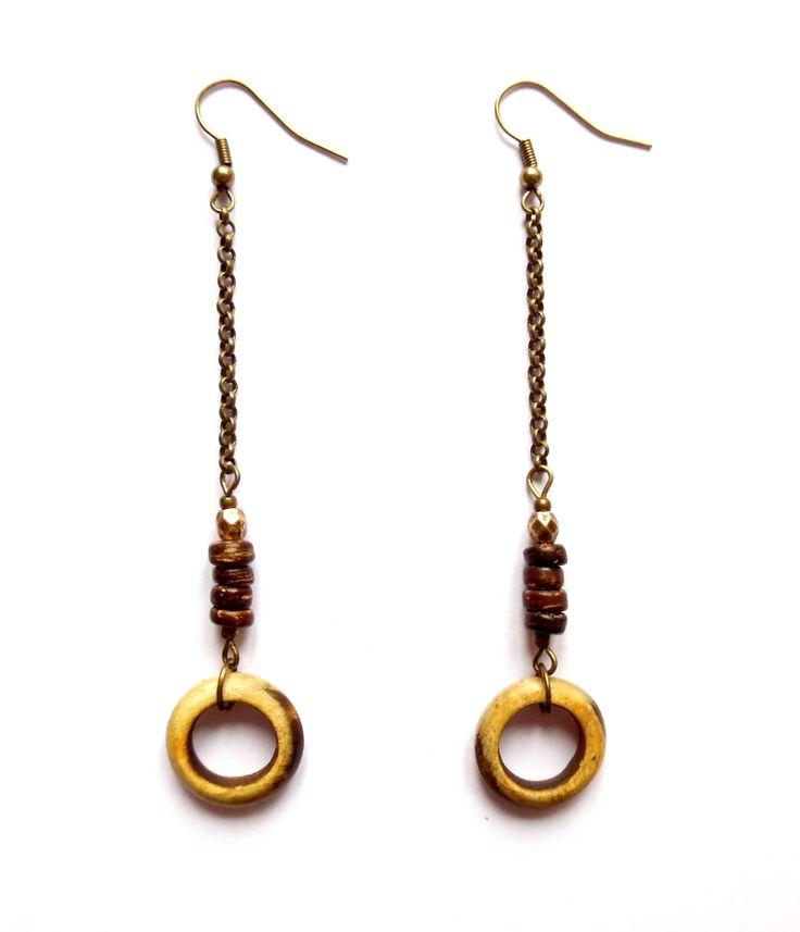 Örhängen i brons med pärlor av kokosnöt och ringar av trä.  Längd: 9,5cm