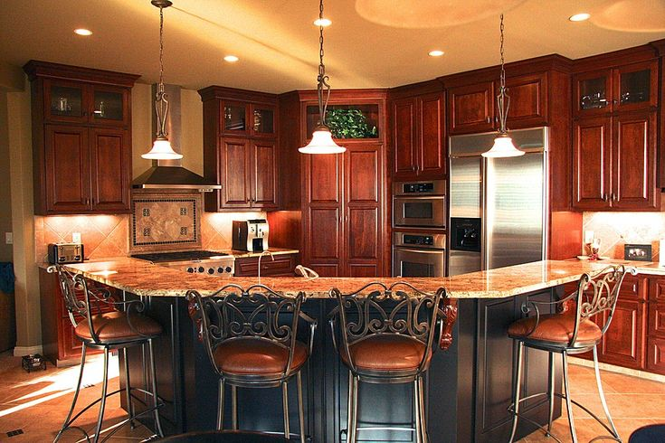 Corner oriented kitchen features cherry wood cabinetry floor to ceiling, with large C-shaped island in black wood with two-tiered marble countertop.