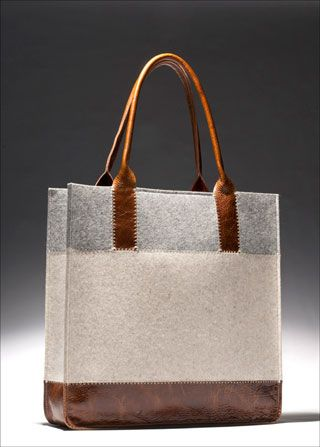 Bag looks like leather, linen and wool (bottom to top) with leather repeated in the handles. Very handsome tote.