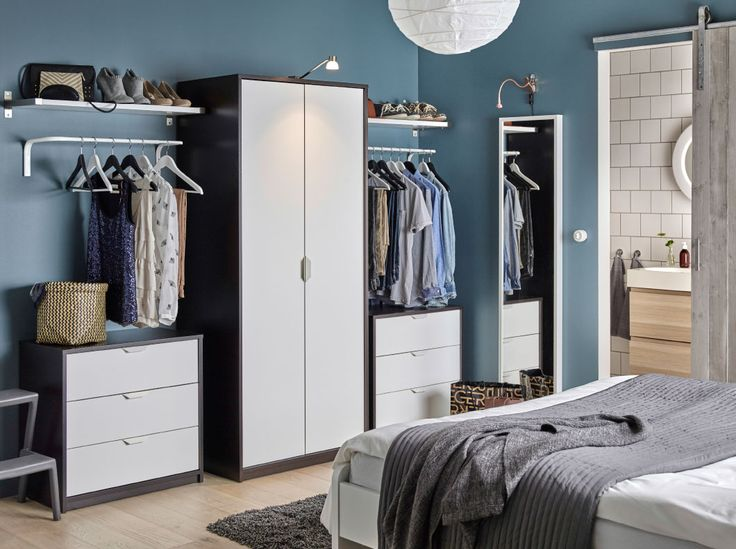 A bedroom with a wardrobe in black-brown with white doors combined with two chest of drawers also in black-brown and white.