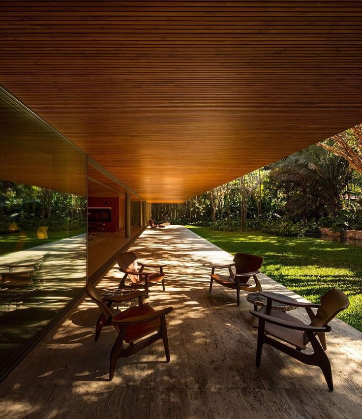 A set of four 'Diz' Armchairs designed by Sergio Rodrigues. Located in a quiet garden-neighborhood in São Paulo and designed by Studio MK27 the 'Ramp House' promotes a radical spatial continuity between the interior and exterior not only through large panes of sliding glass doors - that can be fully opened connecting the living room with the garden. (: Fernando Guerra)
